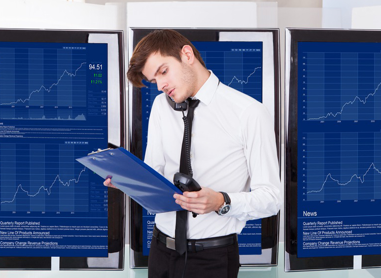 Stock Broker Using Telephone Sitting In Front Of Desktop