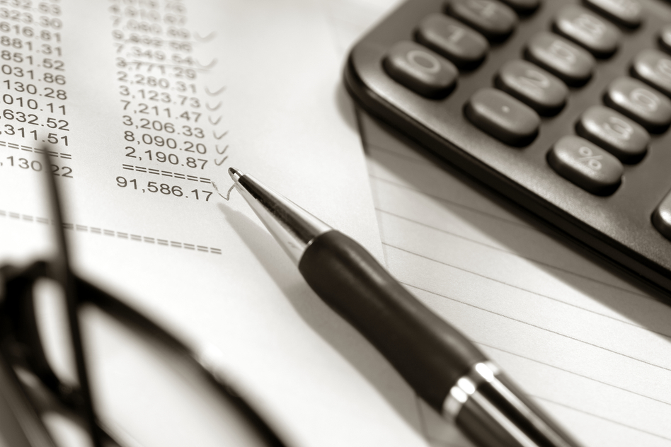 Ballpoint ink pen with calculator and glasses on financial spreadsheet with columns and rows of numbers checked with check marks after account reconciliation